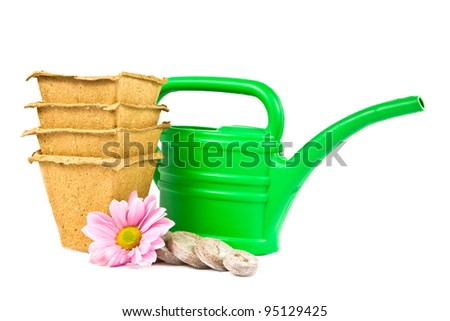 A few peat pellets , pots and watering for growing seedlings on a white background. - stock photo
