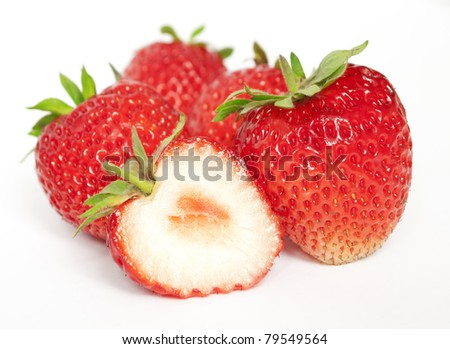 A few ripe strawberries. A one berry is cutted - stock photo