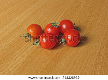 a few small red tomatoes lying on a wooden surface