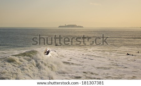 a few surfers on the San Francisco Bay, in front of the Isle of Alcatraz - stock photo