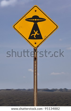 A fictional road sign warning of possible alien abduction. - stock photo