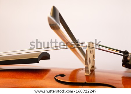 A fiddlestick (violin bow) on the violin string during playing. - stock photo