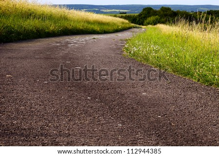 A fields asphalt road in the evening sun, summer, by Honzrath, Saarland/Germany, - stock photo