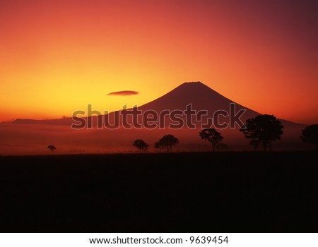 A fiery sunrise over the silhouette of sacred Fuji - stock photo