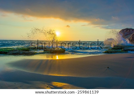 A fiery sunset on a Mediterranean coastal beach in the Middle East. Waves splash against the colorful rocks and the sky is somewhat cloudy. - stock photo