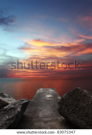 A fiery sunset over a surreal cloudy sky at a concrete jetty in Batu Ferringhi, Penang, Malaysia. - stock photo