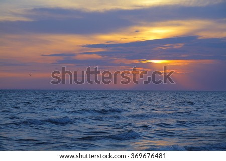 A fiery tropical sunset on a California coastal beach. Colorful dramatic sky with clouds - stock photo