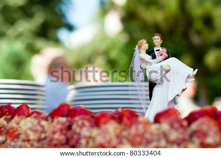 a figure of a bridal couple stands on a cake - stock photo