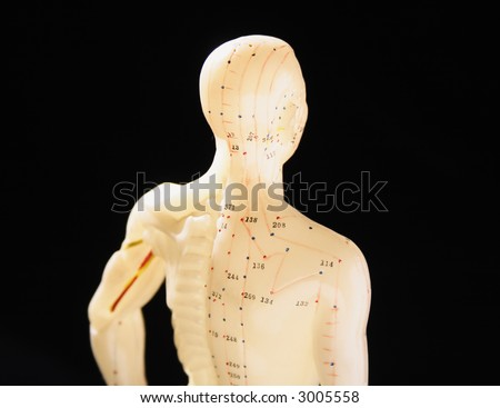 a figure showing acupuncture points, isolated against a black background - stock photo