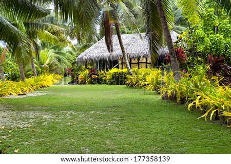 A Fijian bure along a lush, tropical beach surrounded by palm trees, green grass and many plants. - stock photo