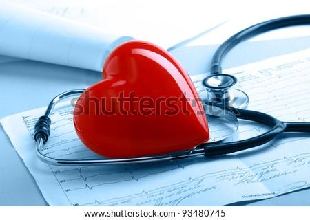 A file folder, a stathoscope and a heart on ekg - stock photo