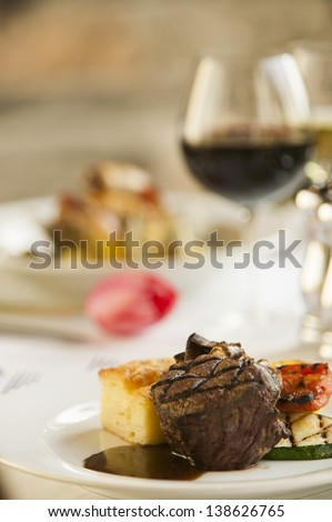 A fillet mignon steak dinner with a glass of red wine and a tulip in a fine restaurant setting. - stock photo