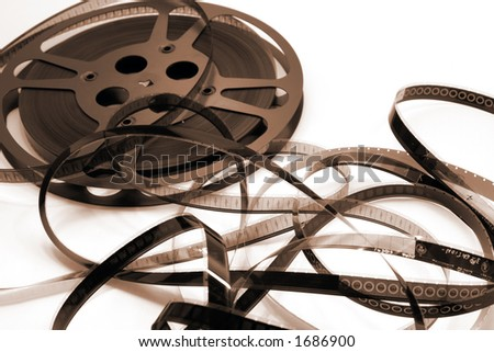 A film reel unwinds and spills into a spaghetti mess.  Focus is on the film strip with 3 and 4 viewable. - stock photo