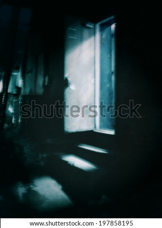 A filtered abstract scene of a dark alleyway at night with light shining through an open doorway - stock photo