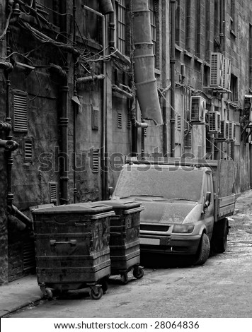 A filthy looking works van parked next to a trash can in a dirty city back street alley in Glasgow. - stock photo