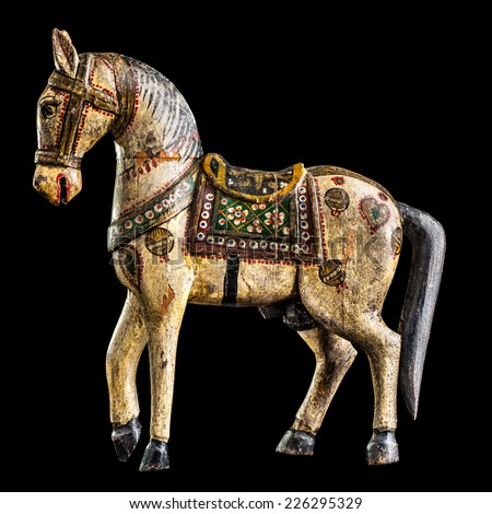 a finely decorated ancient wooden horse isolated over a black background - stock photo