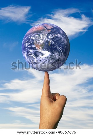A finger balancing the whole earth with the concepts of environmental awareness and balancing the global economy - stock photo