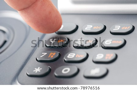 A finger dialing on a phone keypad - stock photo