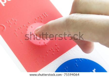 a finger lighting up braille text - stock photo