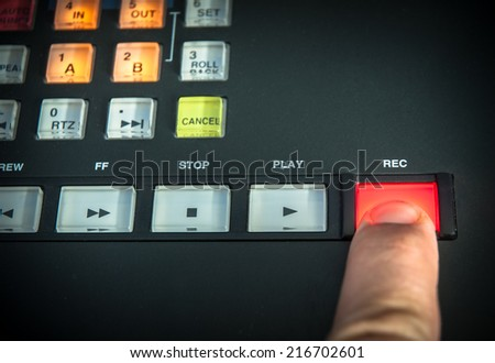 A finger pressing the record button on a digital recorder. - stock photo