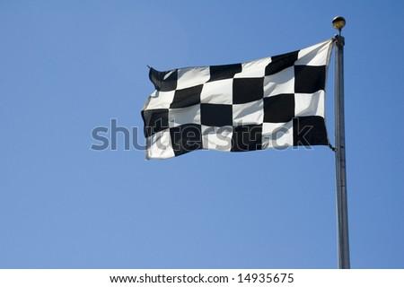 A finish line flag on a pole at a raceway. - stock photo