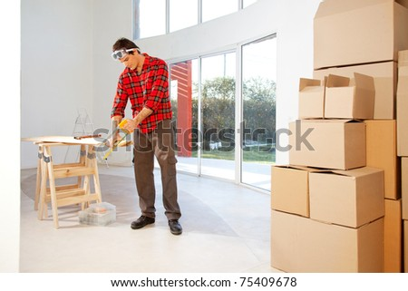 A finishing carpenter cutting wood in a house - stock photo