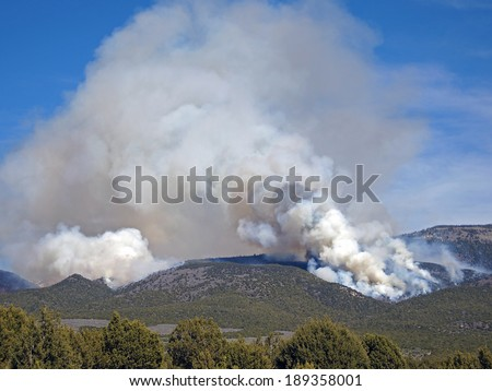 A fire burns through forest and range land on a mountain ridge. - stock photo