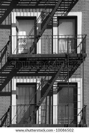 A fire escape with four windows shot in the late afternoon. Black and White - stock photo