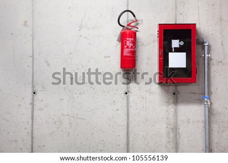 A fire extinguisher and a fire-hose on concrete wall - stock photo