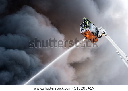 A fire fighter at work in a hydraulic hoist - stock photo