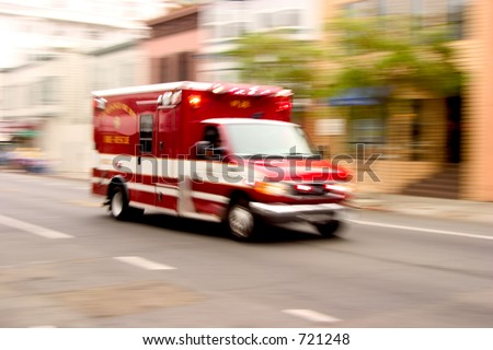 A fire rescue vehicle blazes by, it's sirens whaling.  An intensional zoom blur gives a feeling of a rushed tension to the scene. - stock photo