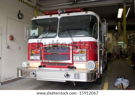 A fire truck is parked in the bay with all of the fire fighting equipment and gear ready to go. - stock photo