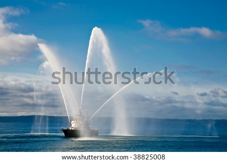 A fireboat casting water stream at open water - stock photo