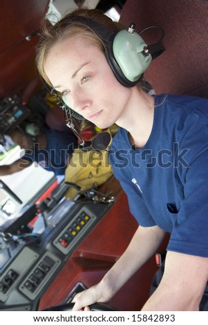 A firefighter driving a fire engine - stock photo