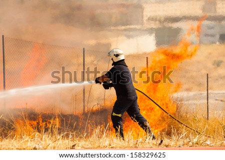 A firefighter extinguish a fire in the forest with a water hose - stock photo