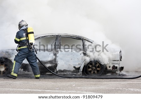a firefighter putting out a car that was burning - stock photo