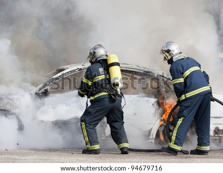 a firefighter putting out a fire - stock photo