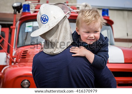 A firefighter take a little child boy to save him. Fire engine car on background. Fireman with kid in his arms. Protection concept - stock photo