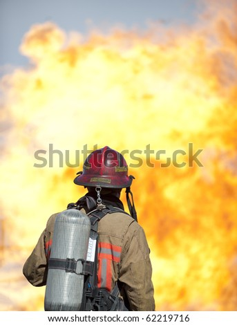 A firefighter watches a training fire. - stock photo