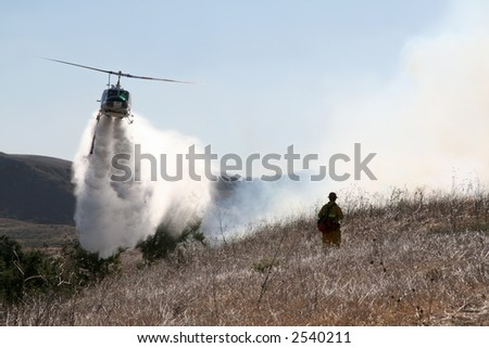 A firefighter watches as a helicopter drops water on a brush fire - stock photo