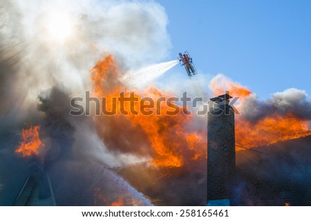 A fireman on an ariel ladder streams water on a burning home from above while others attack from below. - stock photo