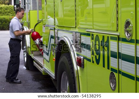 A fireman taking a fire extinguisher out of the rescue truck - stock photo