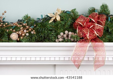 A fireplace mantle is decorated for Christmas with garland, lights, a bow and other decorations. - stock photo