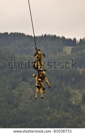 a fireteam of austrian special forces performs a spy rig extraction with a helicopter - stock photo