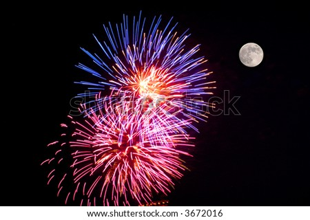 A fireworks display and a full moon. - stock photo