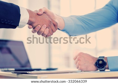 A firm handshake. Confident businessman shaking hands with each other. Close-up view of the hands of a businessman in the office of the table in the formal wear. - stock photo