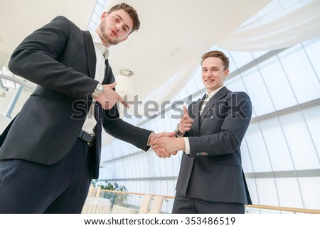 A firm handshake. Two businessman shaking hands with each other and pointing finger at camera