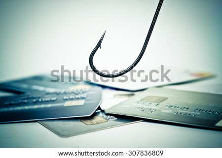 a fish hook over a pile of credit cards - credit card phishing - stock photo