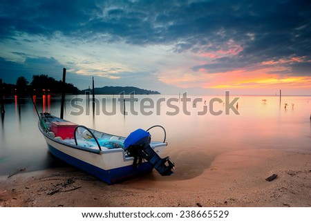 a fisherman boat at the beach. image might contain softness and little noise due to long exposure - stock photo