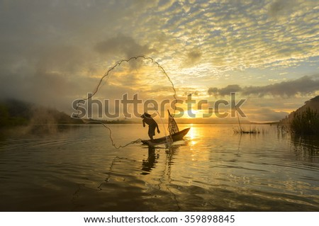 A fisherman casting a net into the water during on the mist at sunrise  - stock photo